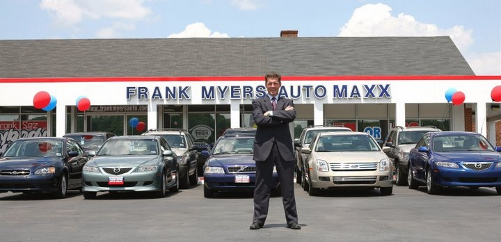 Tracy Myers in front of Frank Myers Auto Maxx Dealership